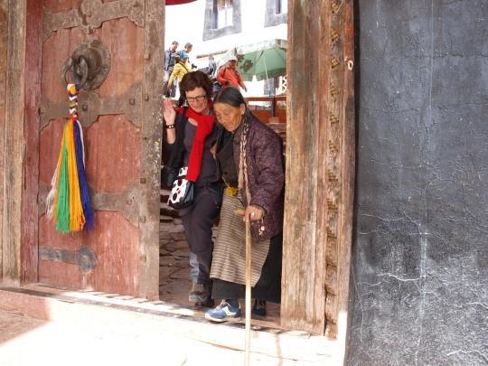 Afien helpt een Tibetaanse pelgrim de steile trappen van het Potala paleis af