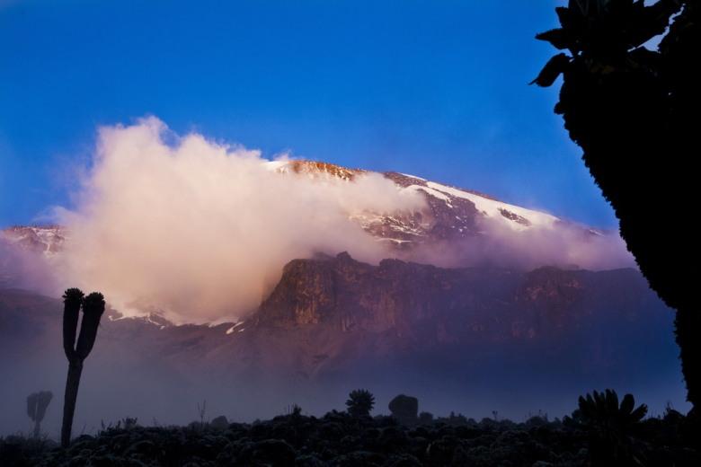 De Kilimanjaro komt uit de wolken met op de voorgrond de Breach wall waar je doorheen moet