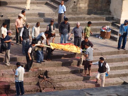 De mannen dragen de lijkbaar naar de Bagmati
