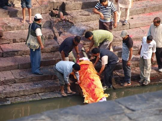 De overleden moeder wordt met haar voeten in de Bagmati gelegd
