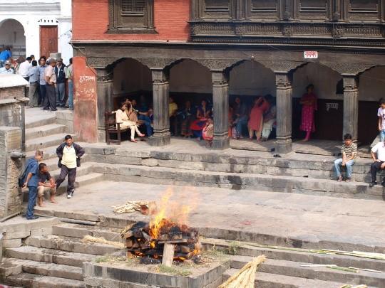 De vrouwen kijken vanonder de tempel toe naar de crematie