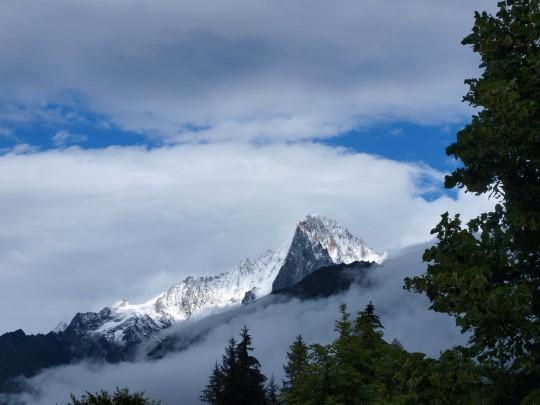 Op een enkel moment komen de hoge toppen van het Mont Blancmassief uit de wolken. Hier de Aiguille Vert.