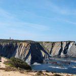 Prachtige rotskliffen met uiteenlopende kleuren, met er boven uitstekend de vuurtoren van Cabo Sardão